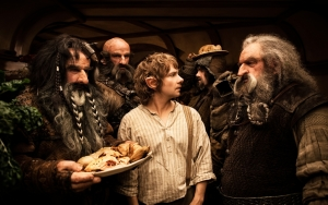 Bilbo (Martin Freeman) bewildered as the dwarves invade his home unexpectedly and immediately make themselves at home by gobbling down his food and liquer.