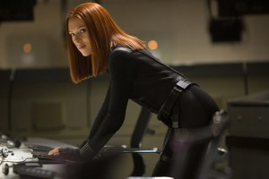 Natasha Romanoff/Black Widow (Scarlett Johansson) bent over a computer, uploading data as part of her mission.