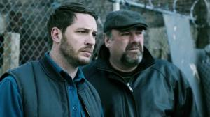 Bob (Tom Hardy) with his boss and cousin, Marv (James Gandolfini, in his final role before his death) outside the back of Cousin Marv's, listening to their Chechen gangster boss.