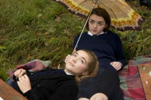 Best friends, Abby (Florence Pugh) and Lydia (Maisie Williams) lying on the grass in their school uniforms, drawing a tree.