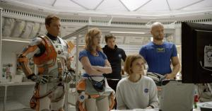 Mark Watney (Matt Damon) with the NASA crew, led by Melissa Lewis (Jessica Chastain, sitting down), before they go out to explore.