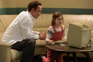 Steve Jobs playing on the Apple Macintosh with his daughter, Lisa (at aged five, played by Makenzie Moss).