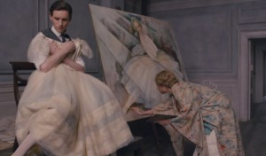 Einar holding a dress as his wife, Gerda (Alicia Vikander), draws him as a woman. Holding the dress, however, awakens Lili.
