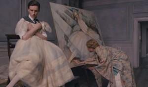Einar holding a dress as his wife, Gerda (Alicia Vikander), draws him as a woman. Holding the dress, however, awakens Lili.