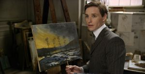 Einar Wegener (Eddie Redmayne), before his transformation, painting a view of his small hometown area.