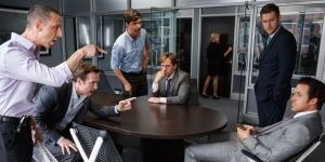 Mark Baum (Steve Carrell, sitting down in the centre), contemplating the horror about to unravel, as his associates shout at Jared Vallett (Ryan Gosling, sitting down, right).