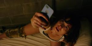 Michelle (Mary Elizabeth Winstead) looking for reception upon waking up to find herself locked in a bunker with her leg in a brace.