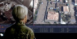 Col Powell looking at an aerial view of the house she wishes to strike (right) and the people she wants to take out inside the house (left). Meanwhile, on the perimeter of the house, Alia sits and sells bread.