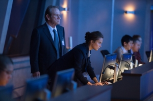 CIA Director Robert Dewey (Tommy Lee Jones) keeping close watch of his bent-forward protégé, Heather Lee (Alicia Vikander).